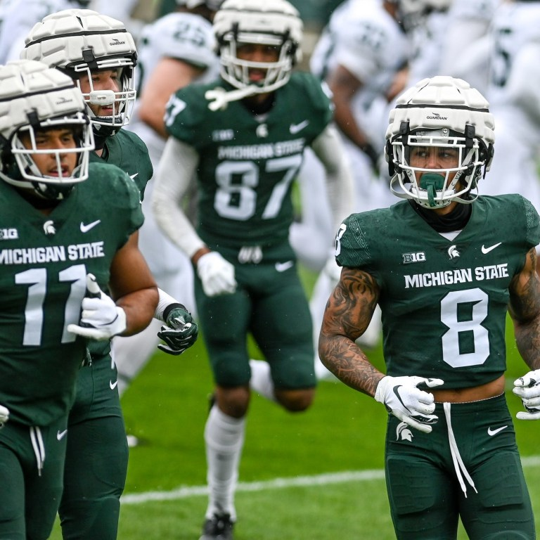 Michigan State's Jalen Nailor, left, runs to the sideline with teammates during the spring football game on April 24 at Spartan Stadium in East Lansing.