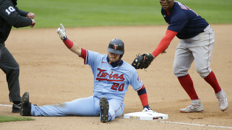 Wednesday, April 14: Minnesota Twins' Josh Donaldson calls for time after safely sliding into third base ahead of the tag of Boston Red Sox third baseman Rafael Devers (11) in the first inning in the second baseball game of a doubleheader.