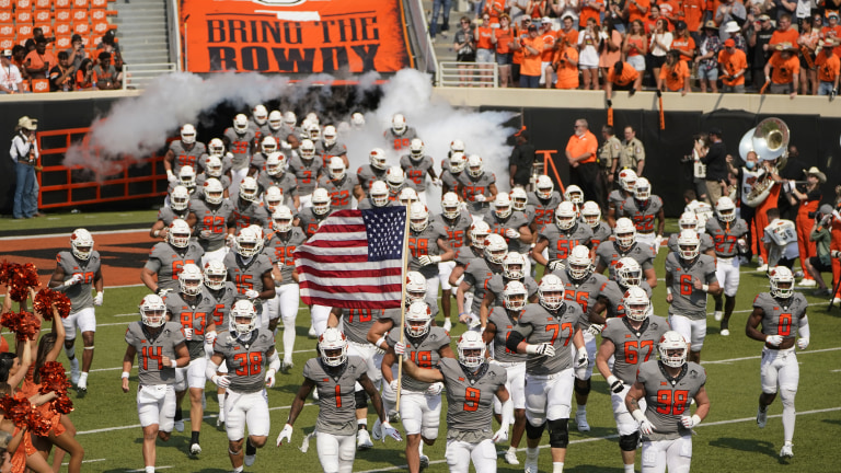 The Oklahoma State Cowboys run onto the field waving the American flag. (AP Photo/Sue Ogrocki)