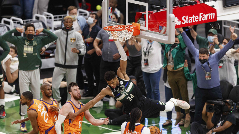 Jul 20, 2021; Milwaukee, Wisconsin, USA; Milwaukee Bucks forward Giannis Antetokounmpo (34) hangs from the rim following a slam dunk during the fourth quarter against the Phoenix Suns during game six of the 2021 NBA Finals at Fiserv Forum. Mandatory Credit: Jeff Hanisch-USA TODAY Sports