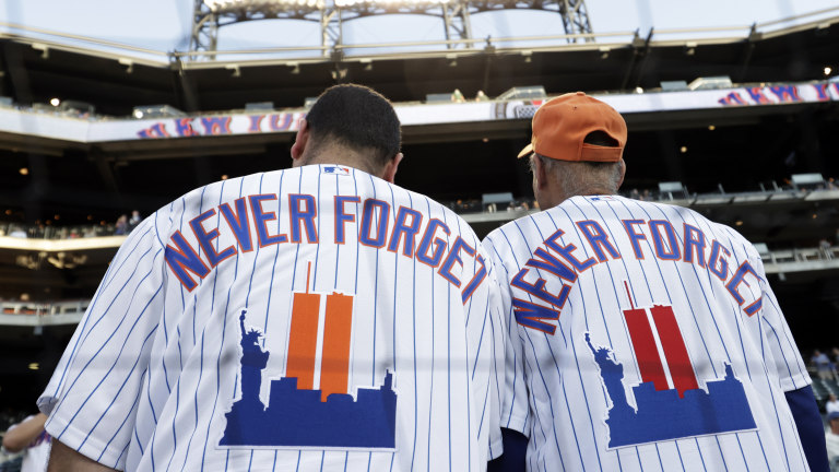 New York Mets fans wear jerseys to remember the 20th anniversary of the 9/11 terrorist attacks before the Yankees-Mets game. (AP Photo/Adam Hunger)