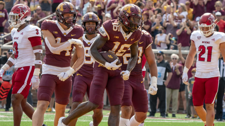 Minnesota Golden Gophers wide receiver Dylan Wright scores in the second quarter, congratulated by teammates wide receiver Brady Boyd, wide receiver Daniel Jackson (9) and Minnesota Golden Gophers running back Bryce Williams at Huntington Bank Stadium.
