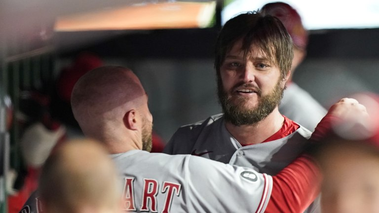 Cincinnati Reds starting pitcher Wade Miley, right, is congratulated by catcher Tucker Barnhart in the dugout after pitching a no-hitter in a baseball game against the Cleveland Indians, Friday, May 7, 2021, in Cleveland. (AP Photo/Tony Dejak)