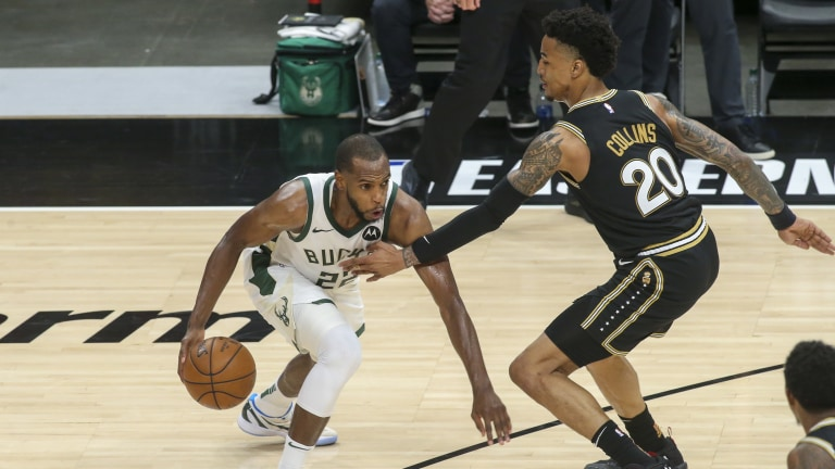 Khris Middleton (22) drives on Atlanta Hawks forward John Collins (20) in the third quarter during game four of the Eastern Conference Finals for the 2021 NBA Playoffs at State Farm Arena. Mandatory Credit: Brett Davis-USA TODAY Sports