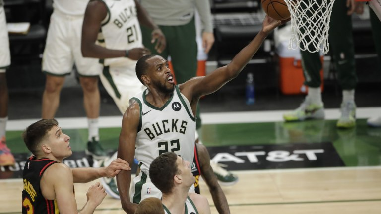 Khris Middleton, center, shoots between multiple Atlanta Hawks defenders during the first half of Game 5 of the NBA Eastern Conference Finals Thursday, July 1, 2021, in Milwaukee. (AP Photo/Aaron Gash)