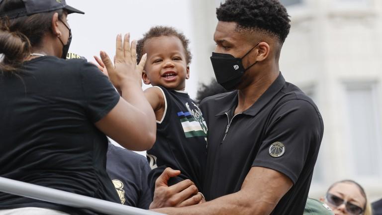 Giannis Antetokounmpo, right, girlfriend Mariah Riddlesprigger and their son Liam celebrate on the parade bus. (AP Photo/Jeffrey Phelps)