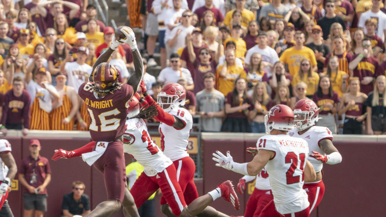 Minnesota Golden Gophers wide receiver Dylan Wright catches a pass over Miami (OH) Redhawks defensive back Ja'don Rucker-Furlow, Miami (OH) Redhawks defensive back Cedric Boswell and several other Redhawks defenders at Huntington Bank Stadium.