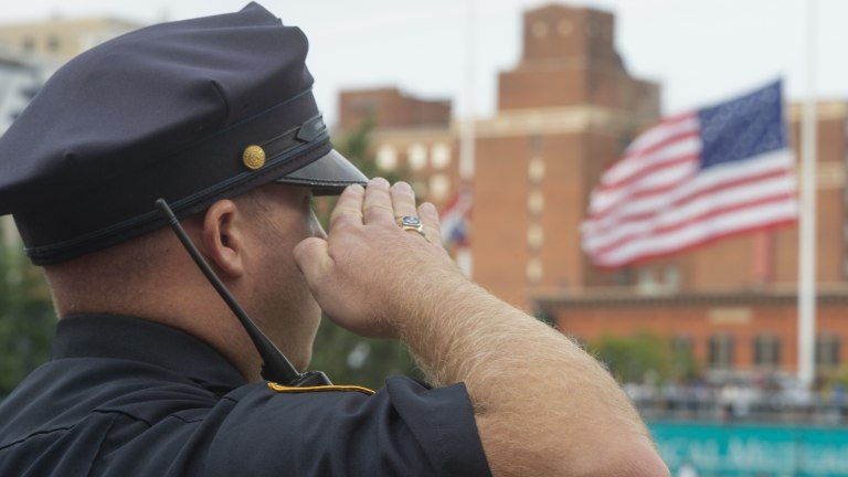 Cleveland Police officer Justin Fisher salutes during the national anthem and a moment of silence before the Cleveland Indians and Milwaukee Brewers play. (AP Photo/Phil Long)