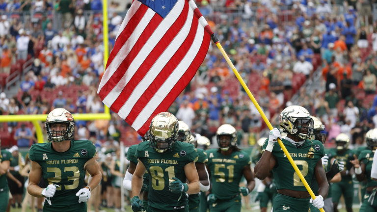 South Florida Bulls defensive back TJ Robinson (2) carries an American flag in remembrance of 9/11 during the first half against the Florida Gators at Raymond James Stadium. (Kim Klement-USA TODAY Sports)