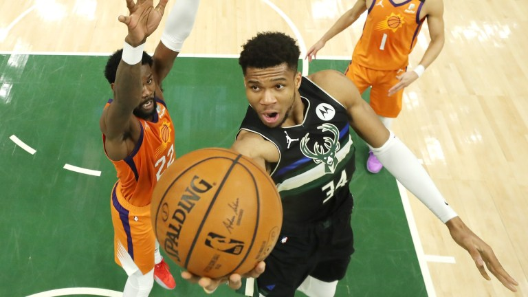 Giannis Antetokounmpo of the Milwaukee Bucks goes up for a shot against Deandre Ayton of the Phoenix Suns during the second half in Game 6 of the NBA Finals at Fiserv Forum.