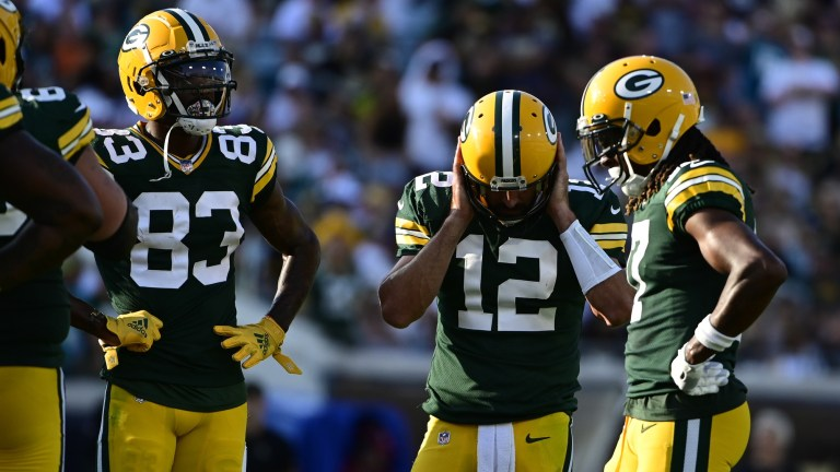 Green Bay Packers quarterback Aaron Rodgers covers his ears in the huddle during the third quarter against the New Orleans Saints at TIAA Bank Field.