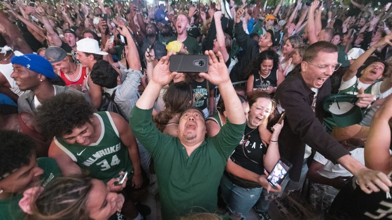 Jul 20, 2021; Milwaukee, Wisconsin, USA; Milwaukee Bucks fans celebrate their first NBA title in 50 years after Game 6 of the NBA Finals in the Deer District outside Fiserv Forum in Milwaukee, Wis. The Milwaukee Bucks beat the Phoenix Suns 105-98 to win the NBA Championship. Mandatory Credit: Mark Hoffman/Milwaukee Journal Sentinel-USA TODAY Sports