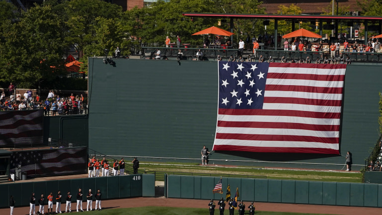 Members of the Baltimore Orioles bullpen, bottom left, stand together as the Ft. McHenry Flag is unrolled during the playing of the national anthem to commemorate the 20th anniversary of the Sept. 11, 2001, terrorist attacks. (AP Photo/Julio Cortez)