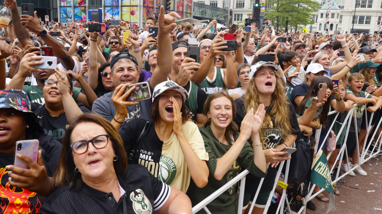Fans scream for Bucks players while watching the buses go by. (AP Photo/Jeffrey Phelps)