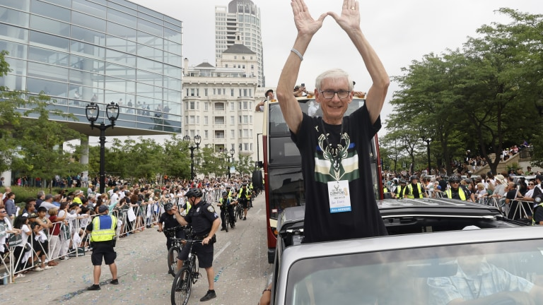 """Wisconsin Governor Tony Evers throws up the """"W"""" during the parade. (AP Photo/Jeffrey Phelps)"""