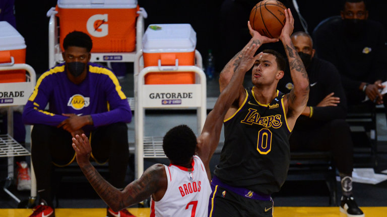 May 12, 2021; Los Angeles, California, USA; Los Angeles Lakers forward Kyle Kuzma (0) shoots against Houston Rockets guard Armoni Brooks (7) during the first half at Staples Center. Mandatory Credit: Gary A. Vasquez-USA TODAY Sports