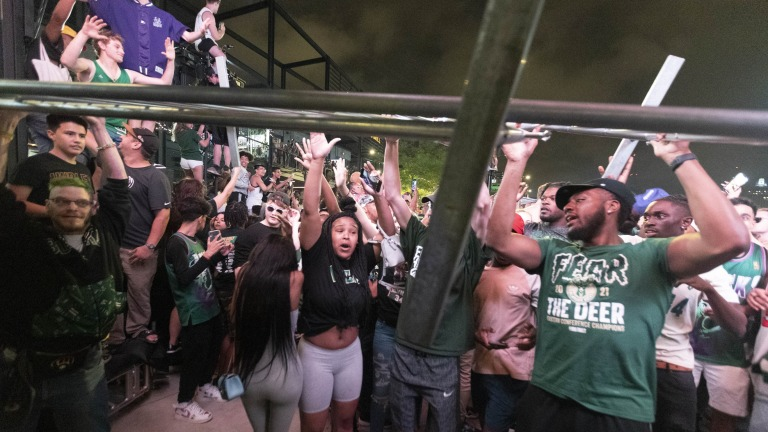 Milwaukee Bucks fans celebrate their first NBA title in 50 years by removing barricades after Game 6 of the NBA Finals in the Deer District.