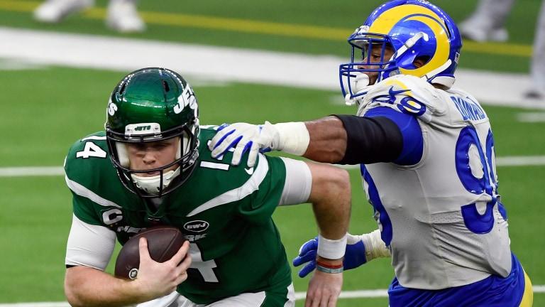 New York Jets former quarterback Sam Darnold tries to run away from Los Angeles Rams defensive end Aaron Donald at SoFi Stadium. Mandatory Credit: Robert Hanashiro-USA TODAY Sports