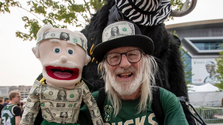 """Ron Workman, age 76, made the five hour drive from Amery to Milwaukee this morning. A puppeteer and ventriloquist, Workman wore a human-sized, wearable gorilla outfit and conducted a puppet. He built the outfit in 1991 and has used it for Brewers and Packers games, adding to it over the years. For the bucks game, he added dollar bills to it to make it """"buck themed."""" Mjs Mjs Bucksfans0005 Jpeg"""