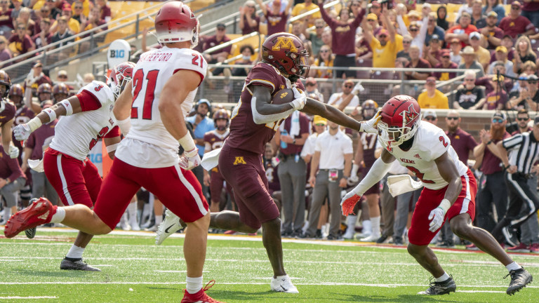 Minnesota Golden Gophers wide receiver Dylan Wright scores in the second quarter, tackled by Miami (OH) Redhawks defensive back Cecil Singleton and defensive back Sterling Weatherford at Huntington Bank Stadium.
