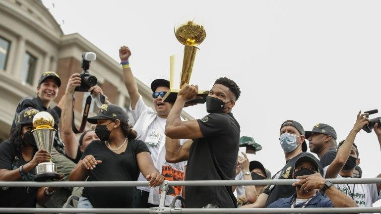 Milwaukee Bucks forward Giannis Antetokounmpo holds the Larry O'Brien NBA Championship Trophy during the Milwaukee Bucks victory parade.