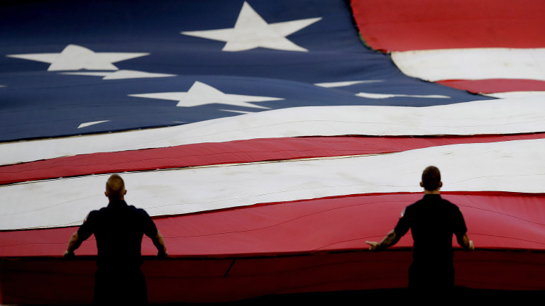 Policemen hold a giant American flag during a pre-game ceremony before the Braves and Marlins begin play. (AP Photo/Ben Margot)