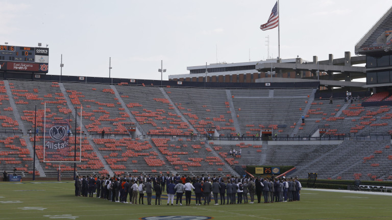 Auburn Tigers players gather at midfield as the American flag is seen at half staff for 9/11 before the game against the Alabama State Hornets at Jordan-Hare Stadium. (John Reed-USA TODAY Sports)