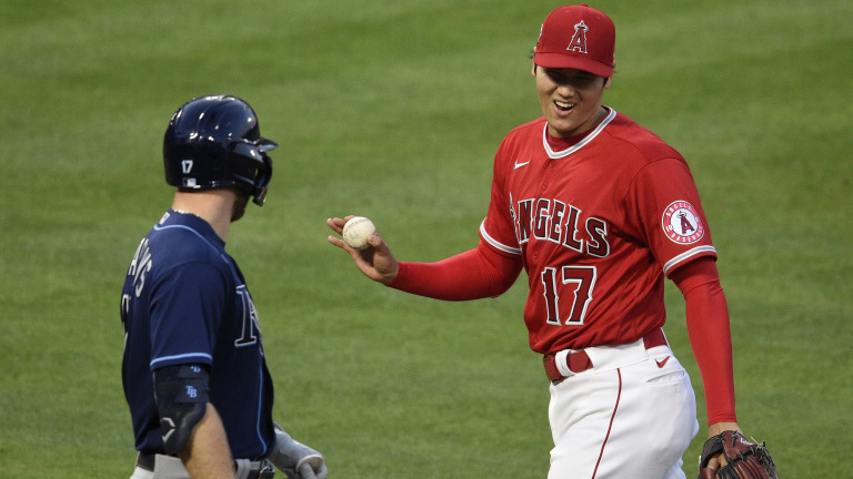 May 5, 2021; Anaheim, California, USA; Los Angeles Angels starting pitcher Shohei Ohtani (17) reacts after catching a ball ball hit by Tampa Bay Rays left fielder Austin Meadows (left) during the third inning at Angel Stadium. Mandatory Credit: Kelvin Kuo-USA TODAY Sports