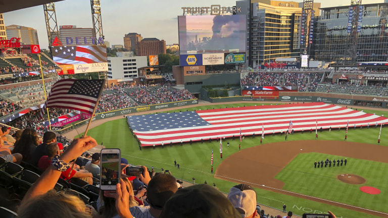 Fans take photos during a pre-game ceremony in remembrance of the 9/11 attacks prior to a game between the Atlanta Braves and the Miami Marlins. (AP Photo/Ben Margot)