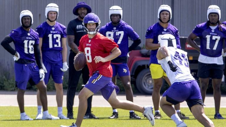 Wednesday, June 9: Minnesota Vikings quarterback Kirk Cousins, left, scrambles during practice in Eagan, Minn.