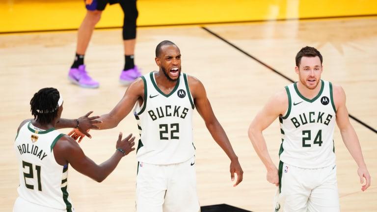 Bucks forward Khris Middleton (22) celebrates with Bucks guard Jrue Holiday (21) and Bucks guard Pat Connaughton (24) against the Phoenix Suns.