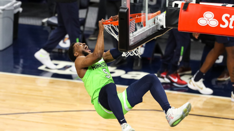 Saturday, March 26: Timberwolves guard Malik Beasley hangs on the rim before a game against the Houston Rockets.