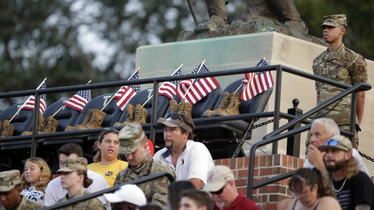 A Troy Army ROTC member stands guard over seats honoring the 13 soldiers killed recently in Afghanistan, during the first half of a game between Troy and Liberty. (AP Photo/Butch Dill)