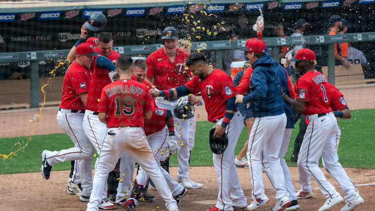 Sunday, July 11: Minnesota Twins teammates mob infielder Jorge Polanco after he smacked a game-winning three-run homer in the bottom of the 10th inning.