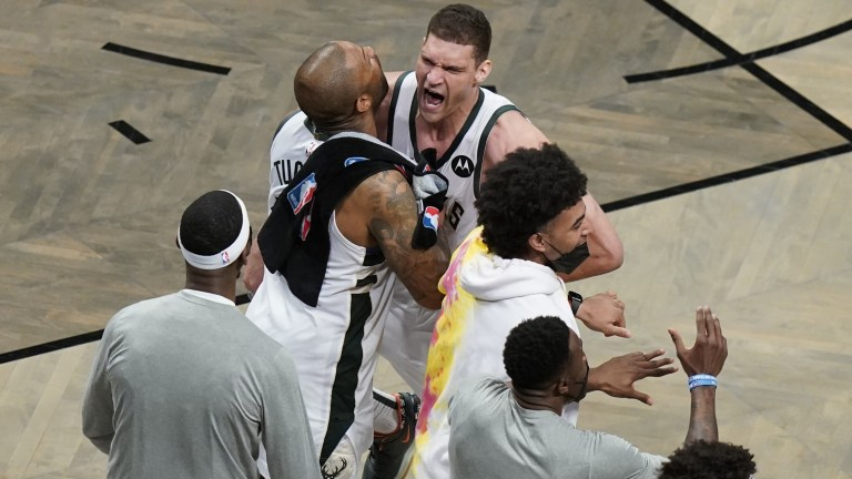Saturday, June 19: Milwaukee Bucks' Brook Lopez celebrates with P.J. Tucker and other teammates during overtime of Game 7 versus the Brooklyn Nets.